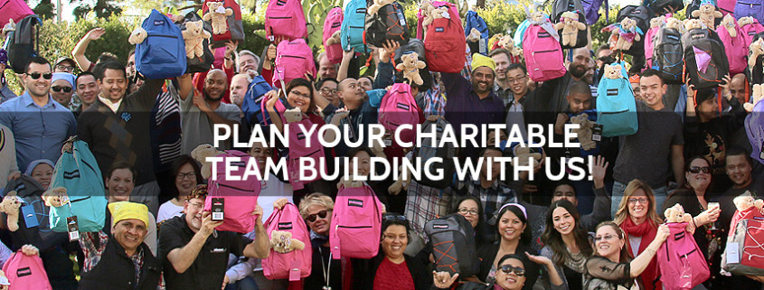 People holding backpacks at charity team building event