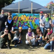 team building graffiti group of adults posed in front of graffiti mural for corporate event