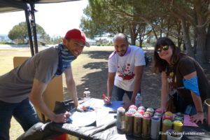 3 adults standing around table for graffiti team building corporate event