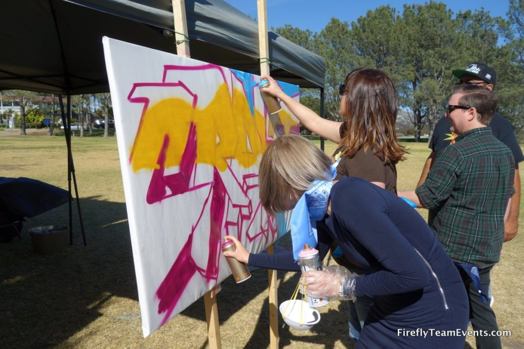 woman spray painting on canvas during graffiti team building corporate event