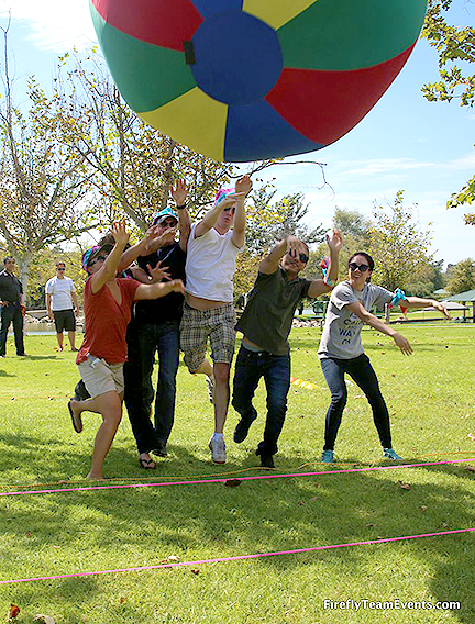 Team throwing oversized ball during corporate team building olympics
