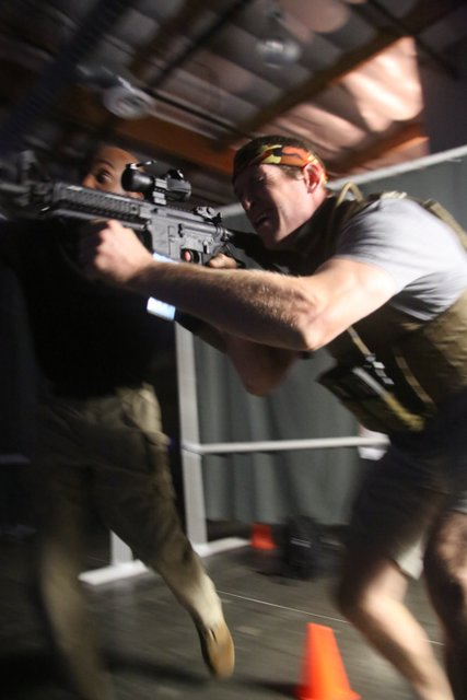 man hold weapon charging toward target on team building event