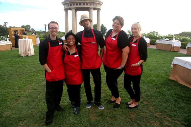 group of adults wearing aprons for cooking competition