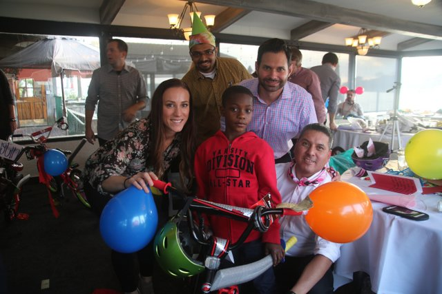 group photo of adults with a child on a bike at a charity team building event