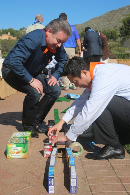 two men build miniature golf hole using canned goods for team building event