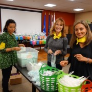 Women in front of baskets filled with donation items for team building charity