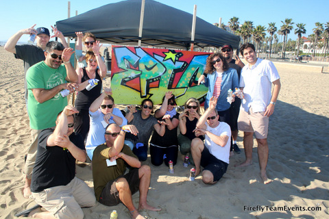 group of adults sitting in front of mural on the beach for graffiti team building event