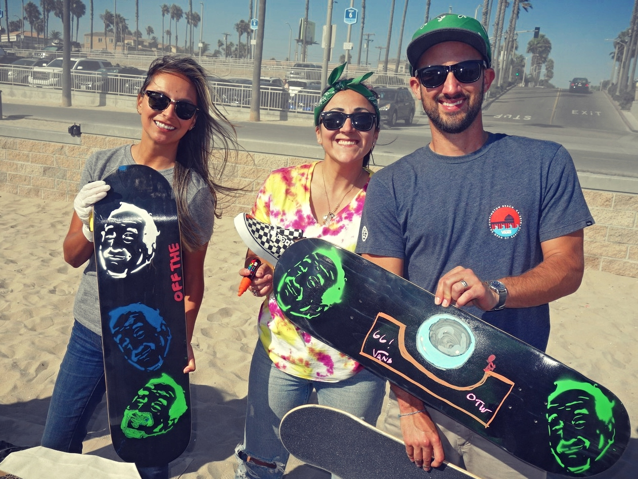 3 adults holding custom skateboard designs for kids on the beach